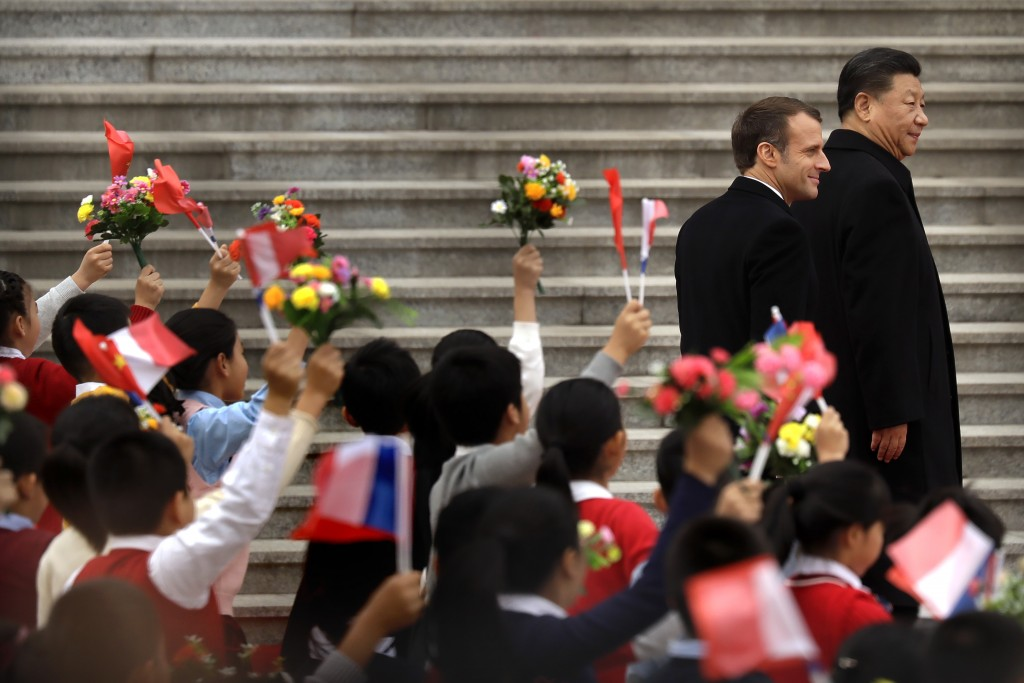 French President Emmanuel Macron, left, and Chinese President Xi Jinping react as schoolchildren wave Chinese and French flags during a welcome ceremo...