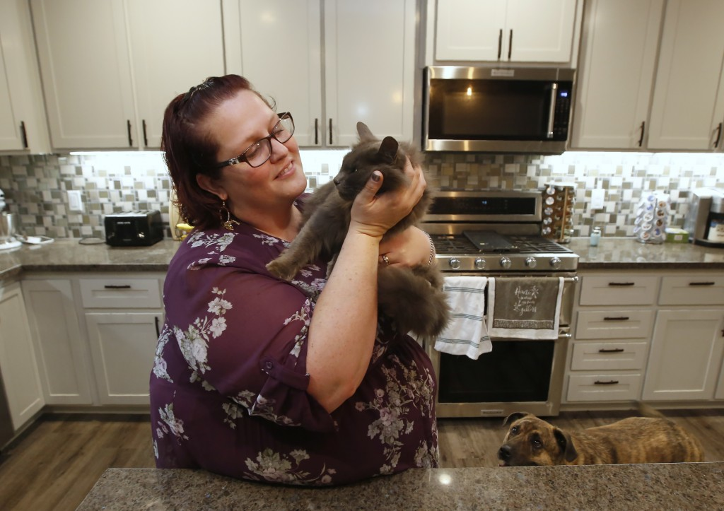 Victoria Sinclaire holds her cat Toby, that survived the Camp Fire, as her dog Joey looks on at her recently rebuilt home in Paradise, Calif., Tuesday...