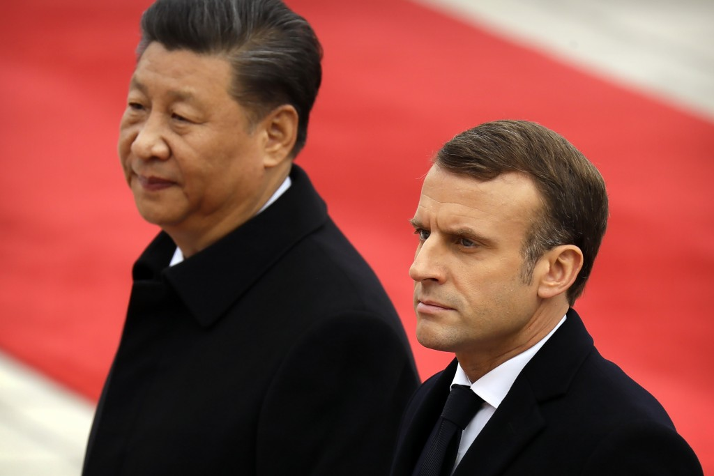 Chinese President Xi Jinping, left, and French President Emmanuel Macron walk together during a welcome ceremony at the Great Hall of the People in Be...
