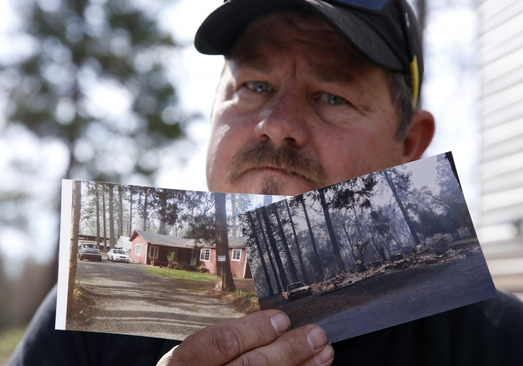 In this Thursday Oct. 24, 2019, photo, Bill Husa displays before-and-after photos of his home lost in last year's Camp Fire in Paradise, Calif. Husa's...