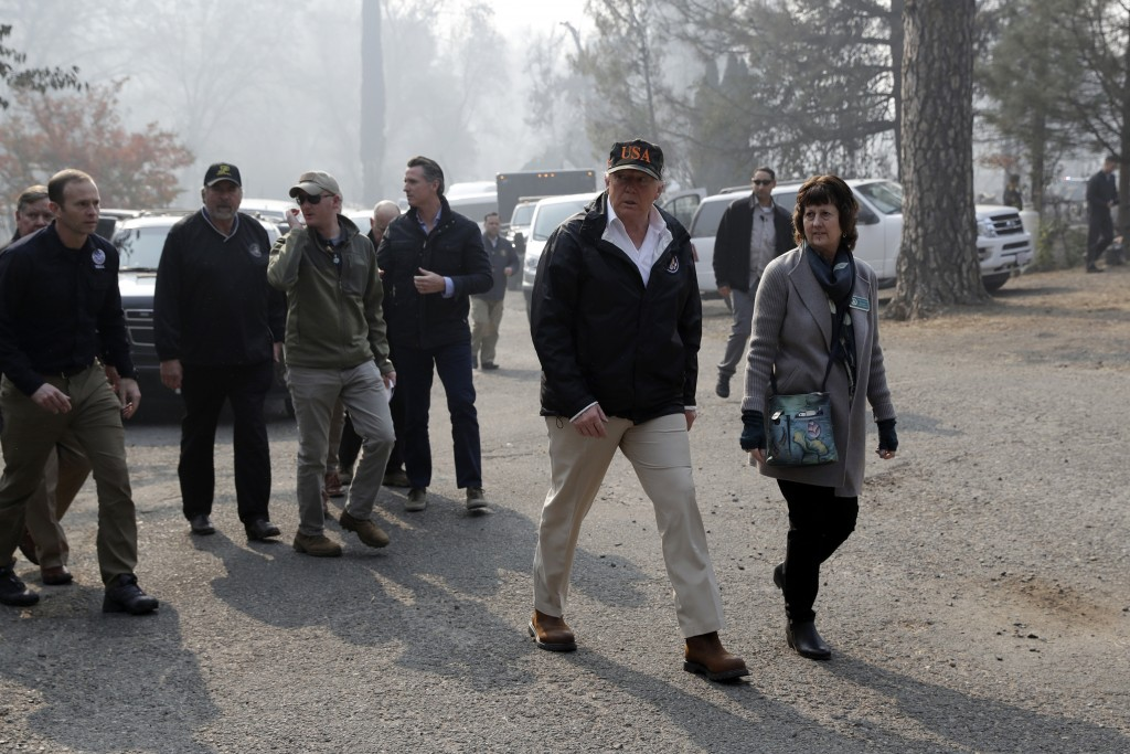 FILE - In this Nov. 17, 2018, file photo, President Donald Trump talks to Mayor Jody Jones as he visits a neighborhood impacted by the wildfires, in P...