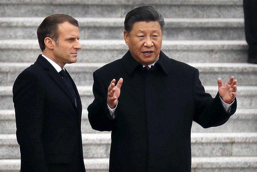 French President Emmanuel Macron, left, listens as Chinese President Xi Jinping talks during a welcome ceremony at the Great Hall of the People in Bei...