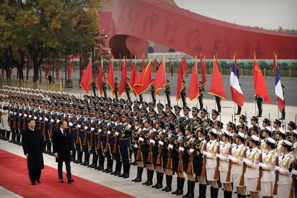 Chinese President Xi Jinping, left, and French President Emmanuel Macron review an honor guard during a welcome ceremony at the Great Hall of the Peop...