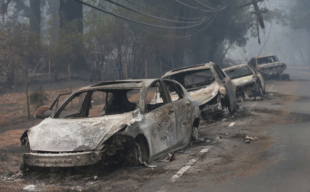 FILE - In this Nov. 9, 2018, file photo, the burned out hulks of cars abandoned by their drivers sit along a road in Paradise, Calif. A lack of escape...