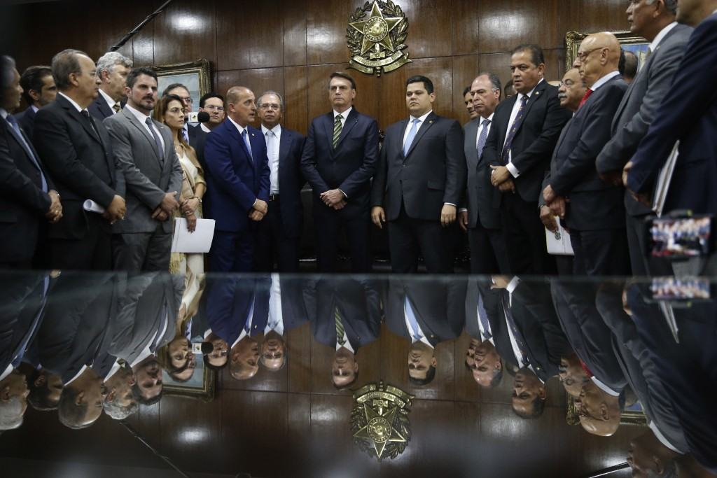 Brazil's President Jair Bolsonaro, center left, next to Senator Davi Alcolumbre, center right, attends the delivery of his government's economic refor...