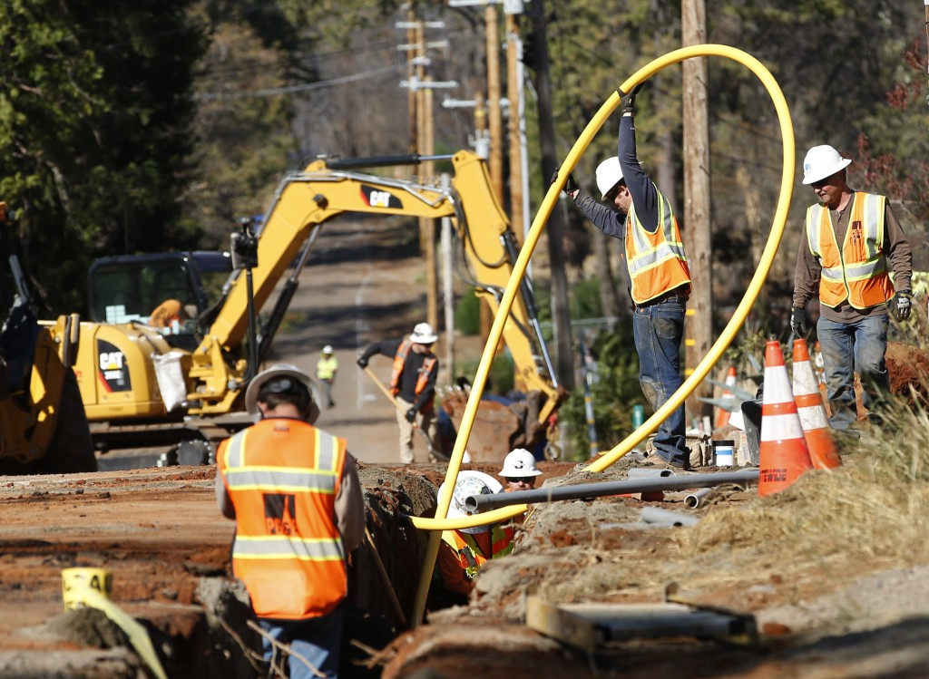 In this Thursday, Oct. 18, 2019, photo, Pacific Gas and Electric Company workmen bury utility lines in Paradise, Calif. Investigators say faulty elect...