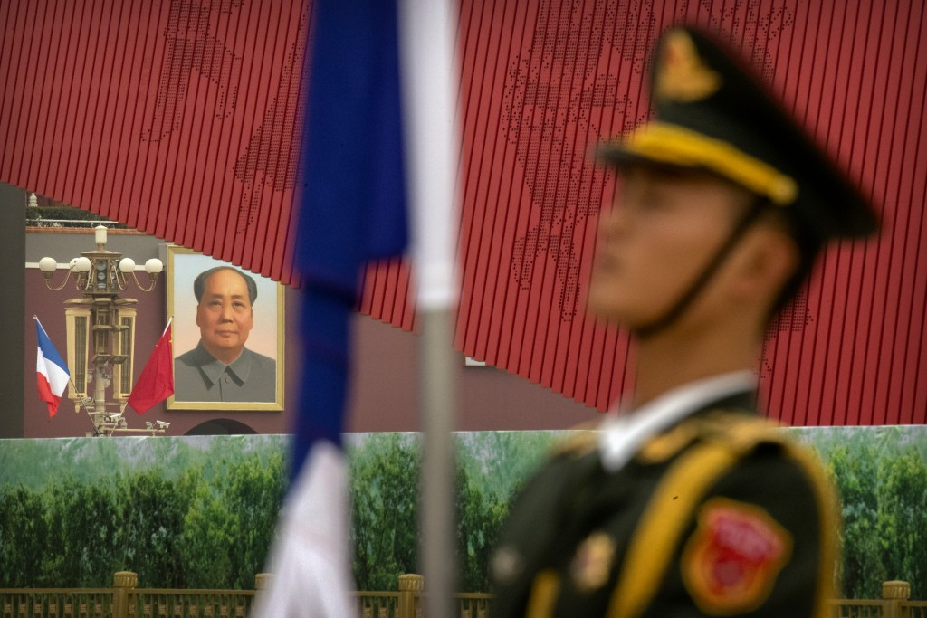 An honor guard member stands at attention as French and Chinese flags fly near the large portrait of Chinese Leader Mao Zedong on Tiananmen Gate befor...