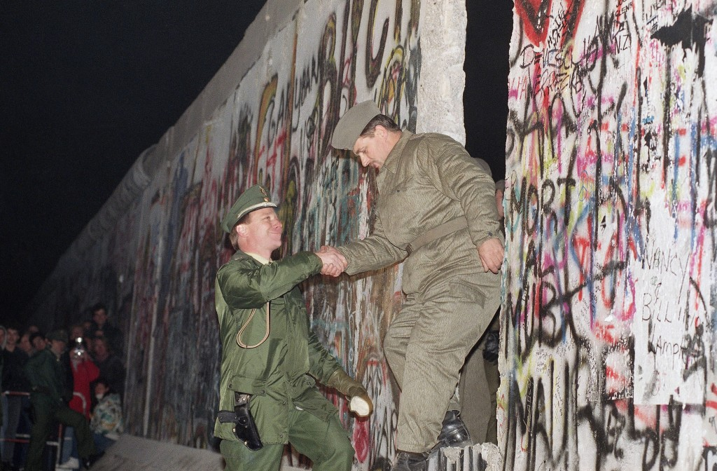 FILE - In this Sunday Nov. 12, 1989 file photo, West German policeman, left, gives a helping hand to an East German border guard who climbs through a ...