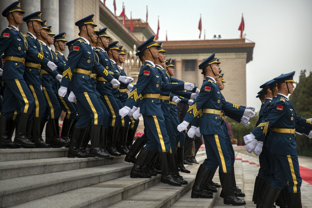 Chinese honor guard members march in formation down the steps of the Great Hall of the People before a welcome ceremony for French President Emmanuel ...