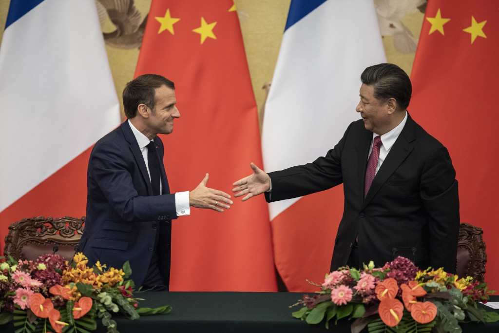 French President Emmanuel Macron, left, shakes hands with Chinese President Xi Jinping following a signing ceremony at the Great Hall of the People in...