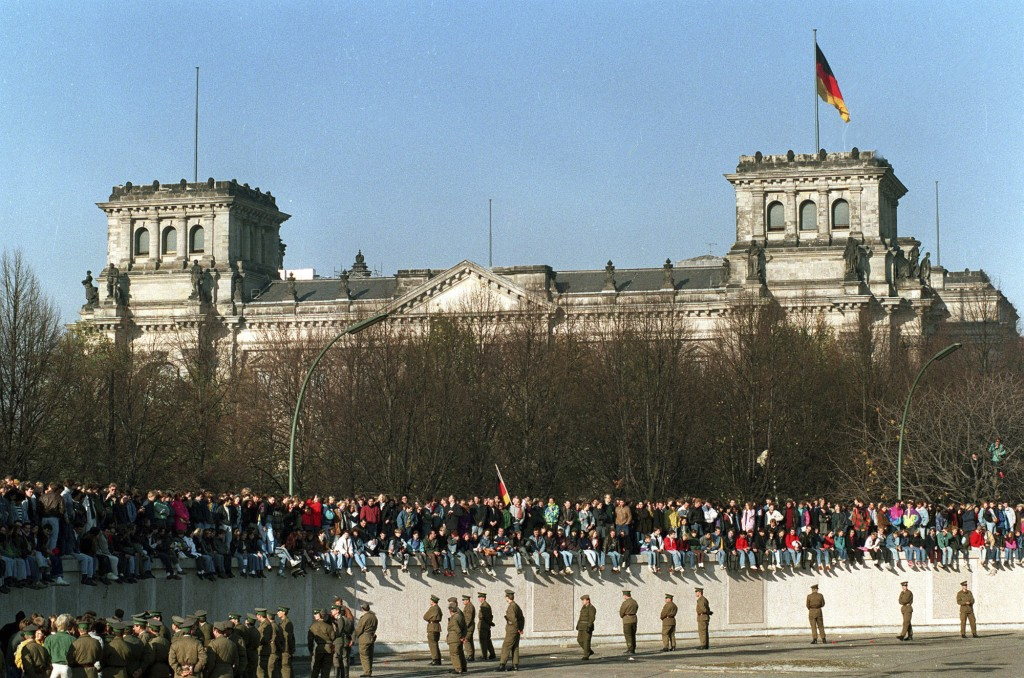 FILE - In this Friday, Nov. 10, 1989 file photo, Germans from East and West stand on the Berlin Wall in front of the the Reichstag Building in Berlin....