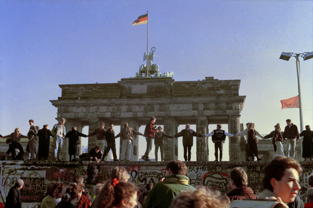 FILE - Friday, Nov. 10, 1989 file photo, Berliners sing and dance on top of the Berlin Wall to celebrate the opening of East-West German borders in Be...