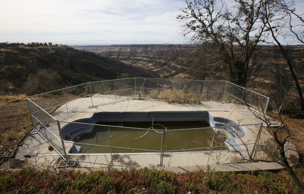 In this photo taken Thursday, Oct. 24, 2019, fencing surrounds a swimming pool at a home that was lost in last year's Camp Fire in Paradise, Calif. On...