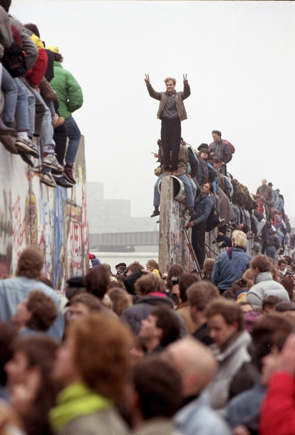 FILE - In this Sunday Nov. 12, 1989 file photo, Berliners celebrate on top of the wall as East Germans (backs to camera) flood through the dismantled ...