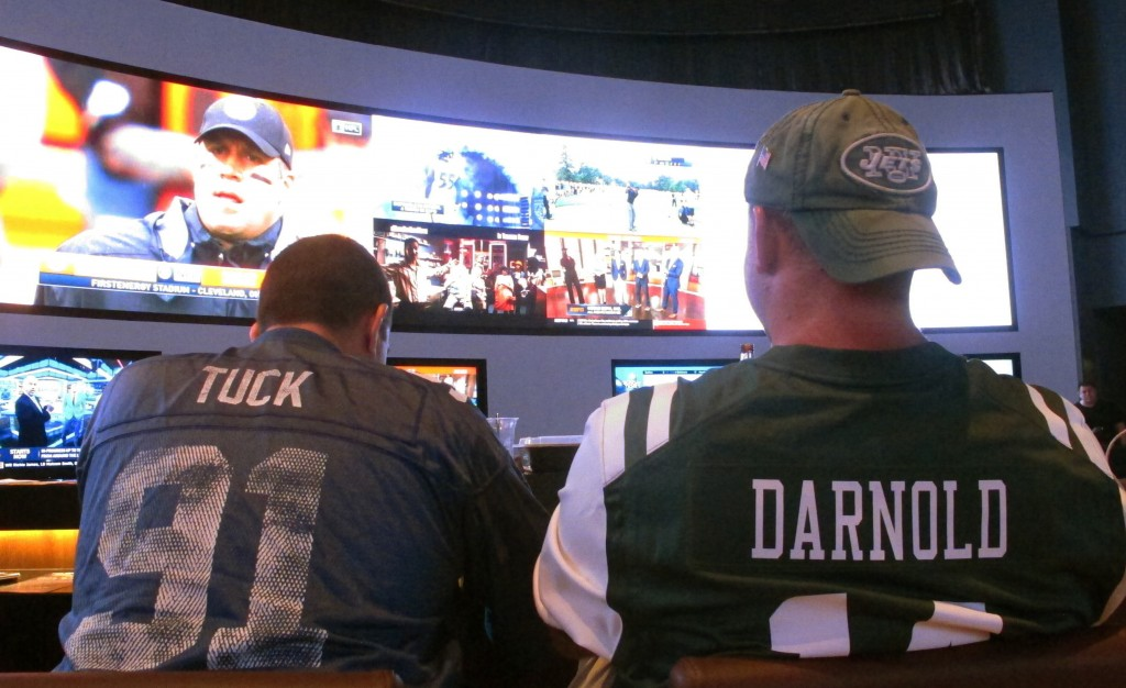 This Sept. 9, 2018 photo shows fans of the New York Giants and Jets watching a football game after placing bets in the sports betting lounge at the Oc...