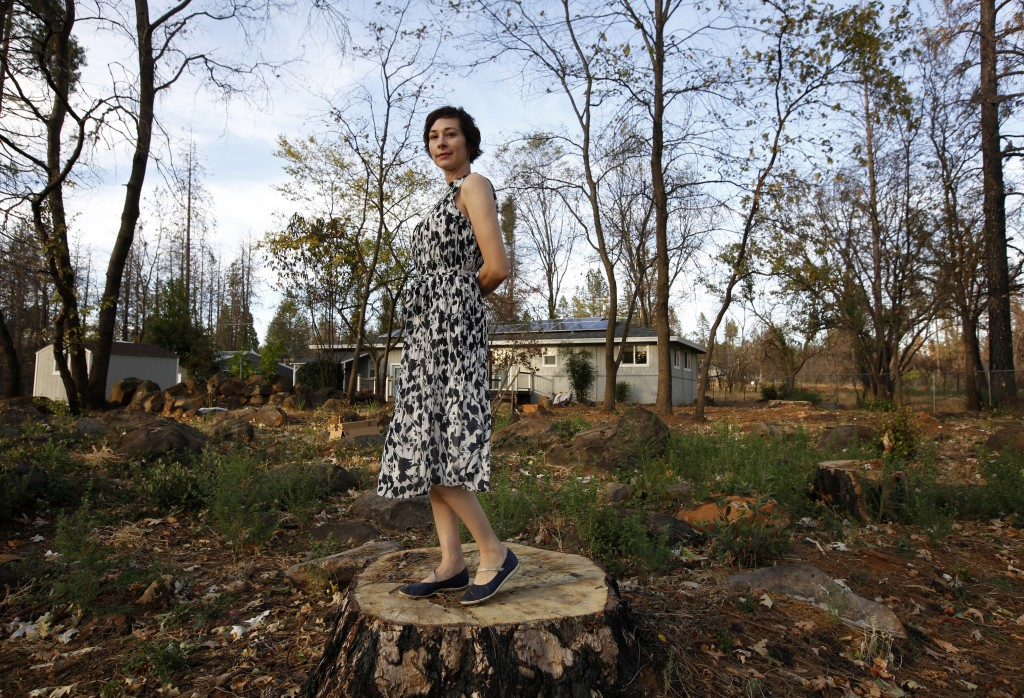 In this Thursday, Oct. 24, 2019, photo, Libby Hail poses at her home that was not destroyed when last year's Camp Fire destroyed nearly 9,000 homes wh...