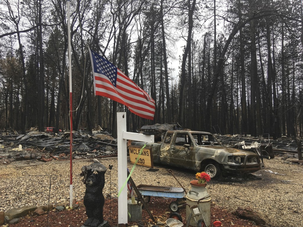 FILE - In this Dec. 5, 2018, file photo, a flag flies amid the remains of Jerry and Joyce McLean's home destroyed by the Camp Fire in Paradise Calif. ...