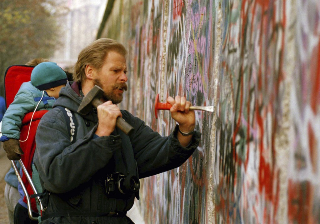 FILE - In this Tuesday Nov. 14, 1989 file photo, a sight-seeing West Berliner carries his baby and uses a hammer and chisel to carve out a piece of th...