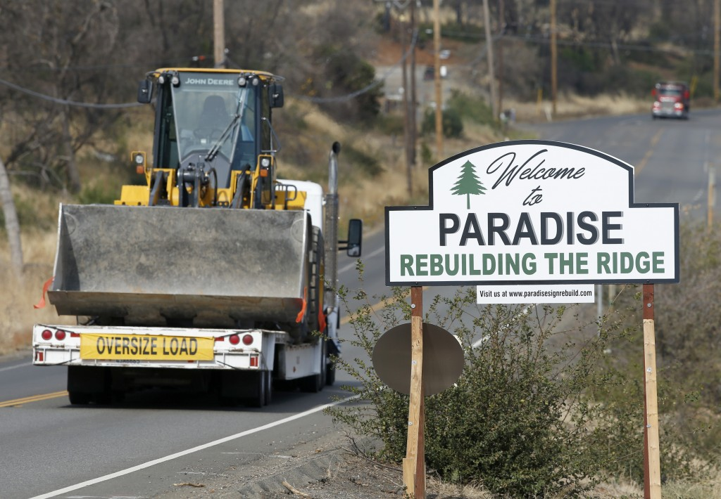 """Vehicles pass a sign welcoming people to Paradise, Calif., Tuesday Nov. 5, 2019. The sign also displays the slogan, """"Rebuilding The Ridge,"""" that has b..."""