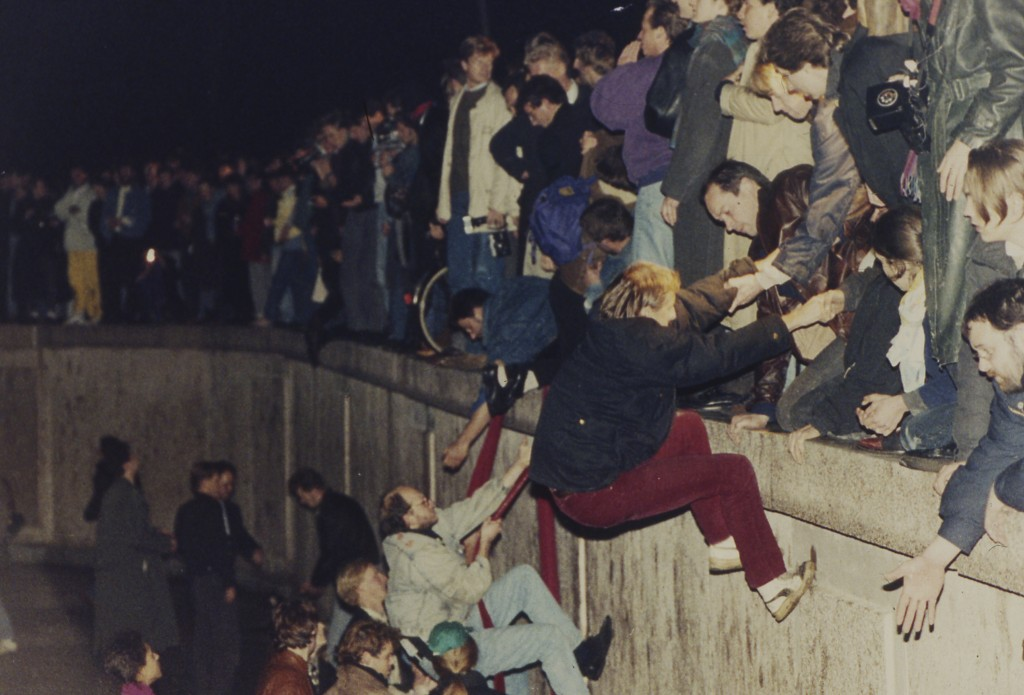 FILE - In this early Friday morning, Nov. 10, 1989 file photo, East Berliners get helping hands from West Berliners as they climb the Berlin Wall whic...