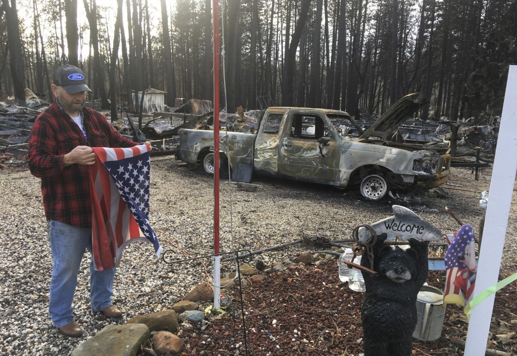 FILE - In this Dec. 5, 2018, file photo, Jerry McLean folds the flag that was flying outside the remains of his home in Paradise, Calif. The home McLe...
