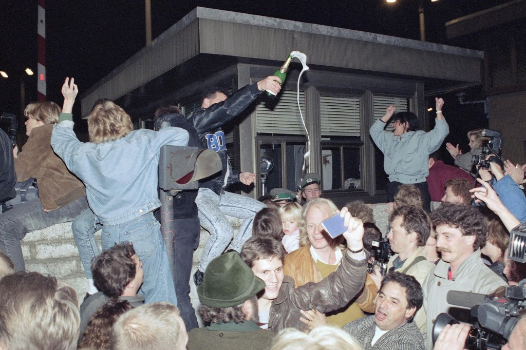 FILE - This Nov. 10, 1989 file photo shows East and West Berliners celebrating in front of a control station on East Berlin territory, during the open...