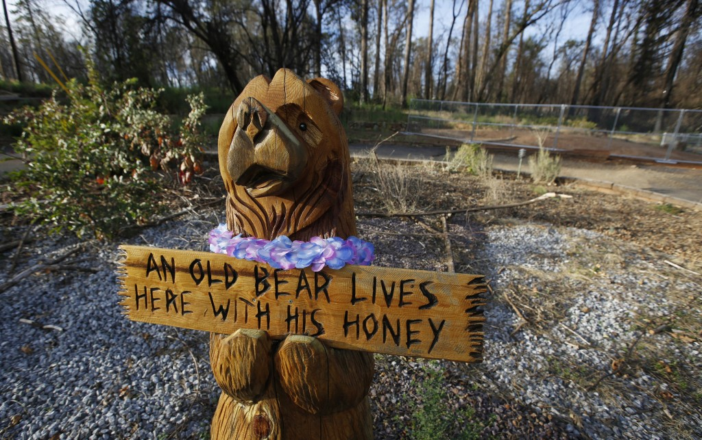 FILE - In this Thursday, Oct. 24, 2019, photo, a wooden bear still stands at a home that was lost in last year's Camp Fire in Paradise, Calif. Only a ...