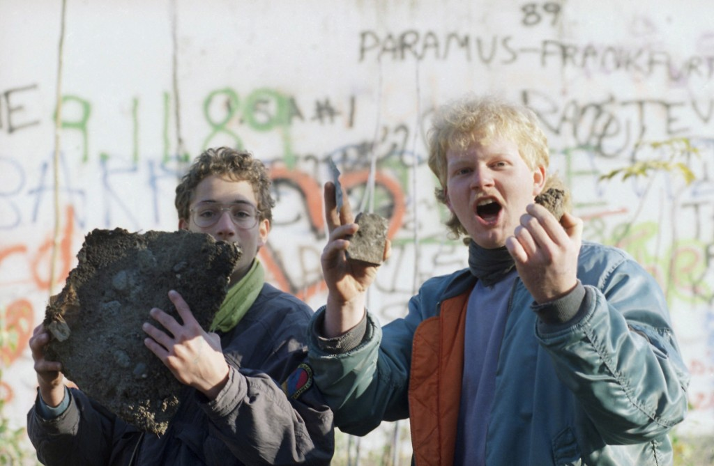 FILE - In this Nov. 10, 1989 file photo Berlin schoolboys proudly show off bricks of the Berlin Wall they found near Brandenburg Gate in Berlin. (AP P...