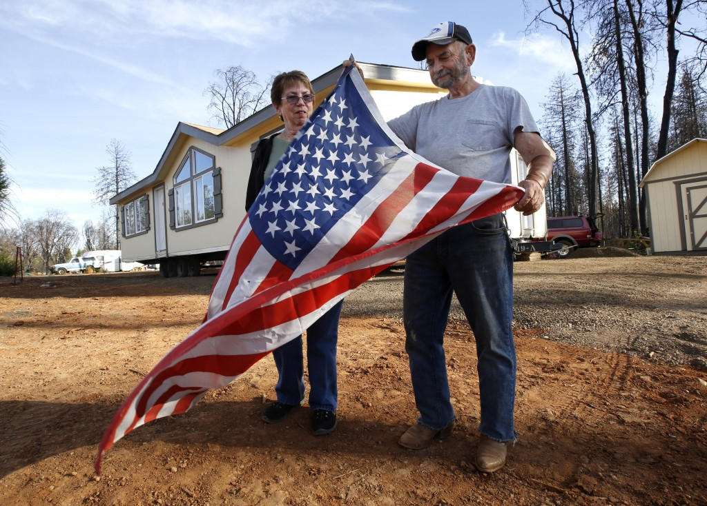 Joyce and Jerry McLean unfurl an American flag outside their new modular home that was recently moved in to replace their home that was destroyed by l...