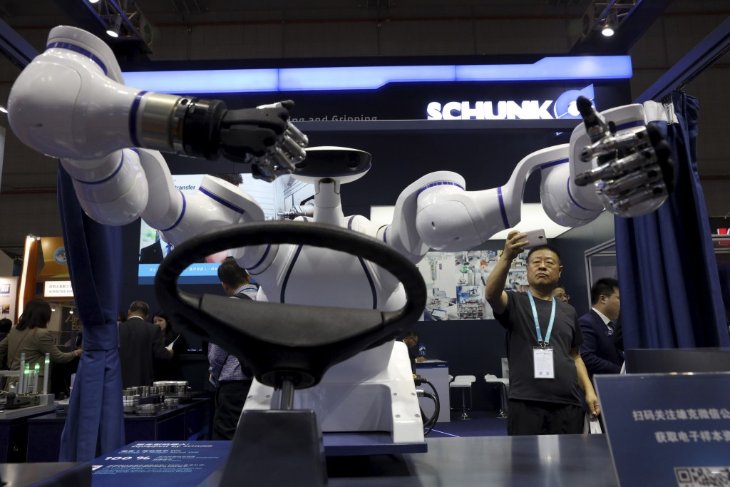 In this Wednesday, Nov. 6, 2019, file photo, a visitor takes a photo of a robot that can be used to operate a vehicle during the China International I...