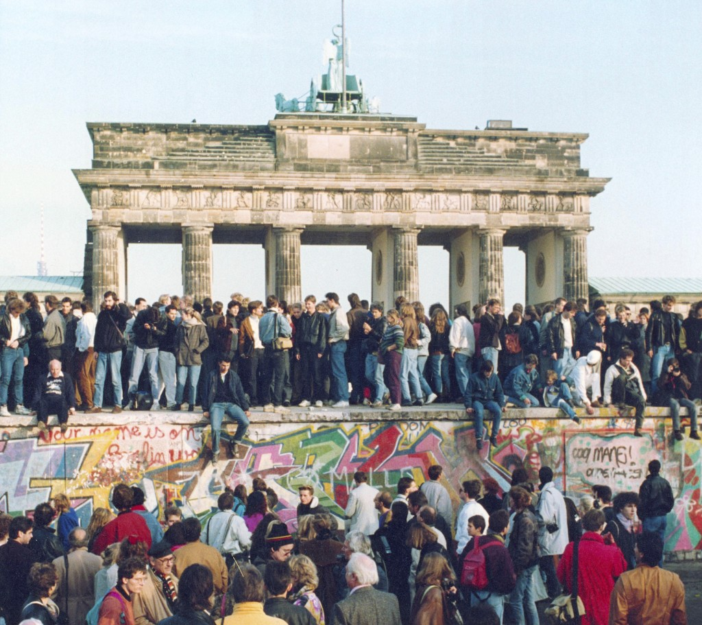 FILE - In this Friday, Nov. 10, 1989 file photo, Germans from East and West stand on the Berlin Wall in front of the Brandenburg Gate in Berlin. (AP P...