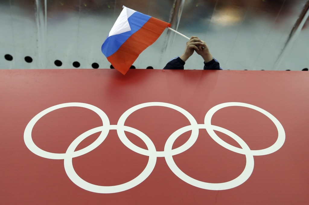 FILE - In this Feb. 18, 2014, file photo, a Russian skating fan holds the country's national flag over the Olympic rings before the men's 10,000-meter...