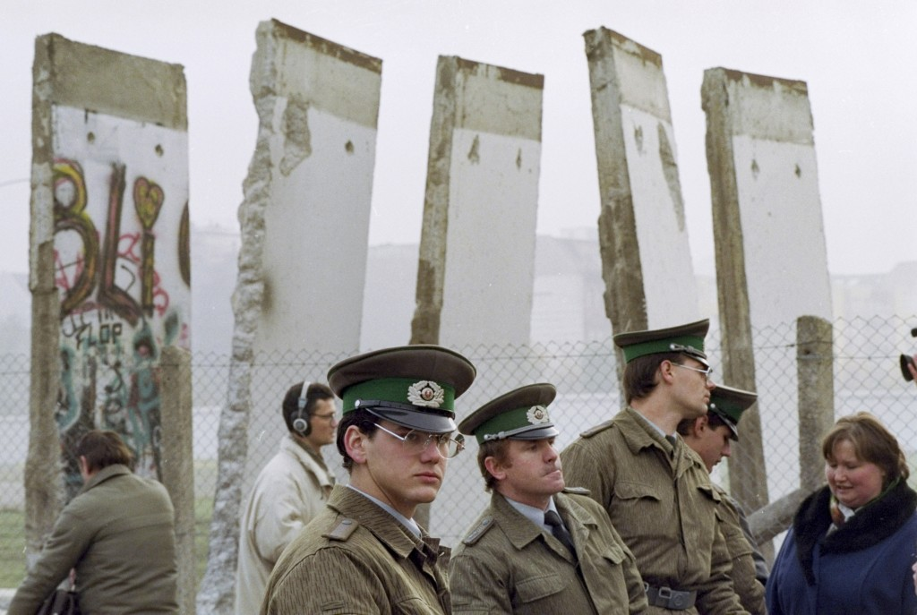 FILE - In this Nov. 13, 1989, file photo, East German border guards stand in front of segments of the Berlin Wall, which were removed to open the wall...