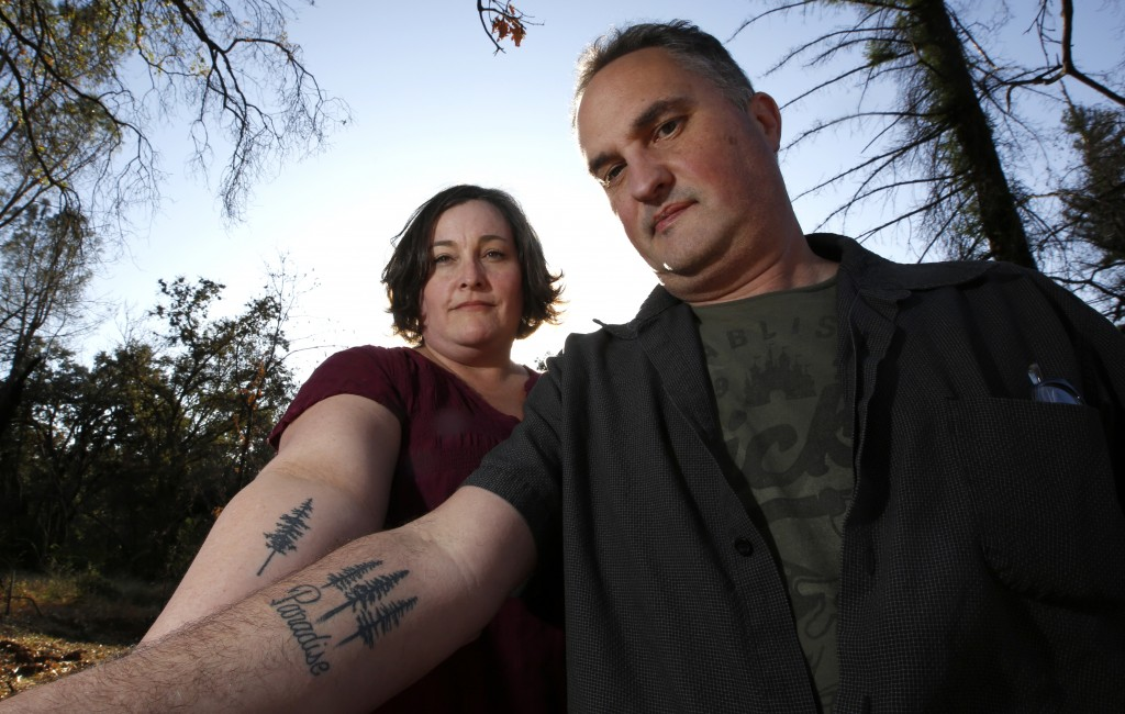 In this Thursday, Oct. 17, 2019, photo, Laura and Chris Smith display their Paradise tattoos they had done to show support for their former community ...