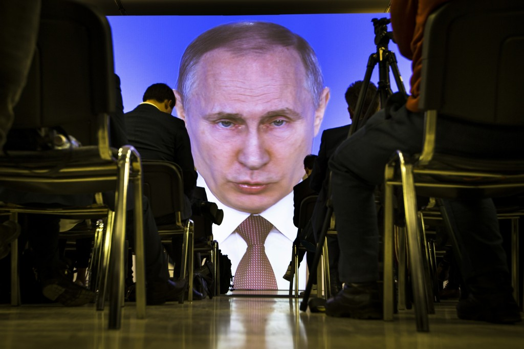 FILE - In this March 1, 2018, file photo, journalists watch as Russian President Vladimir Putin gives his annual state of the nation address in Manezh...