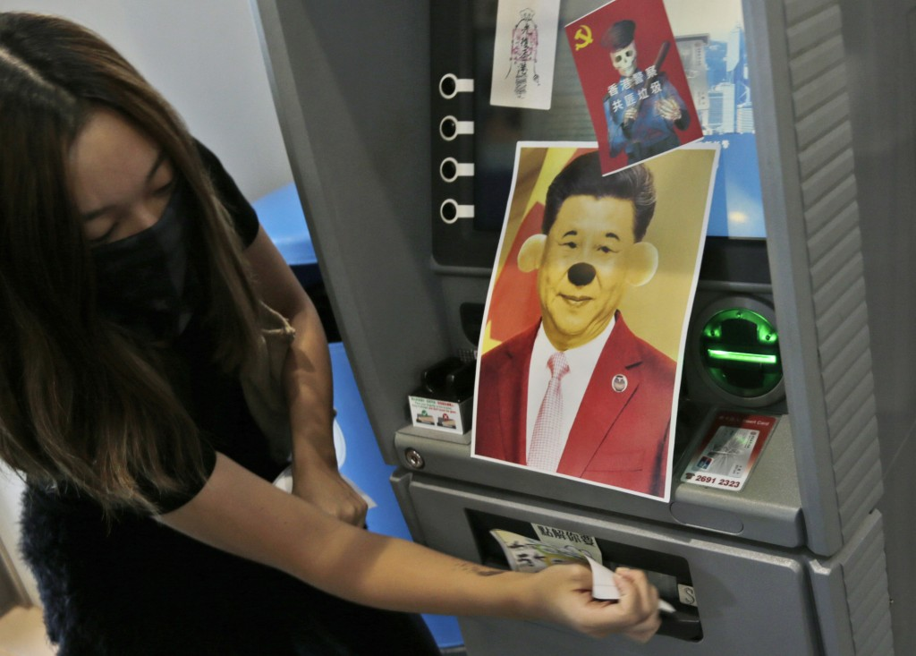 A protester attaches stickers and a defaced portrait of Chinese President Xi Jinping on a Bank of China's ATM machine during an anti-government rally ...