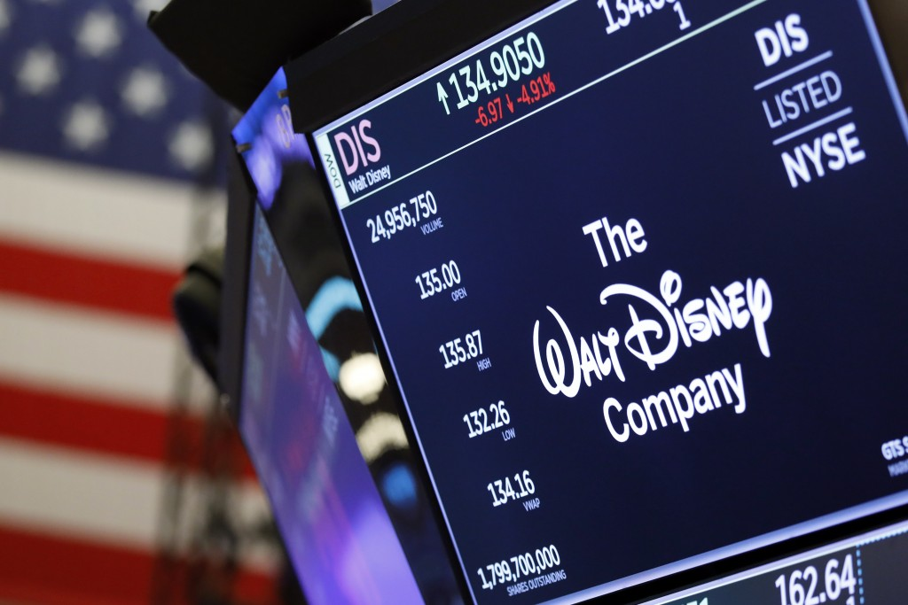 FILE - In this Aug. 7, 2019, file photo the logo for The Walt Disney Company appears above a trading post on the floor of the New York Stock Exchange....