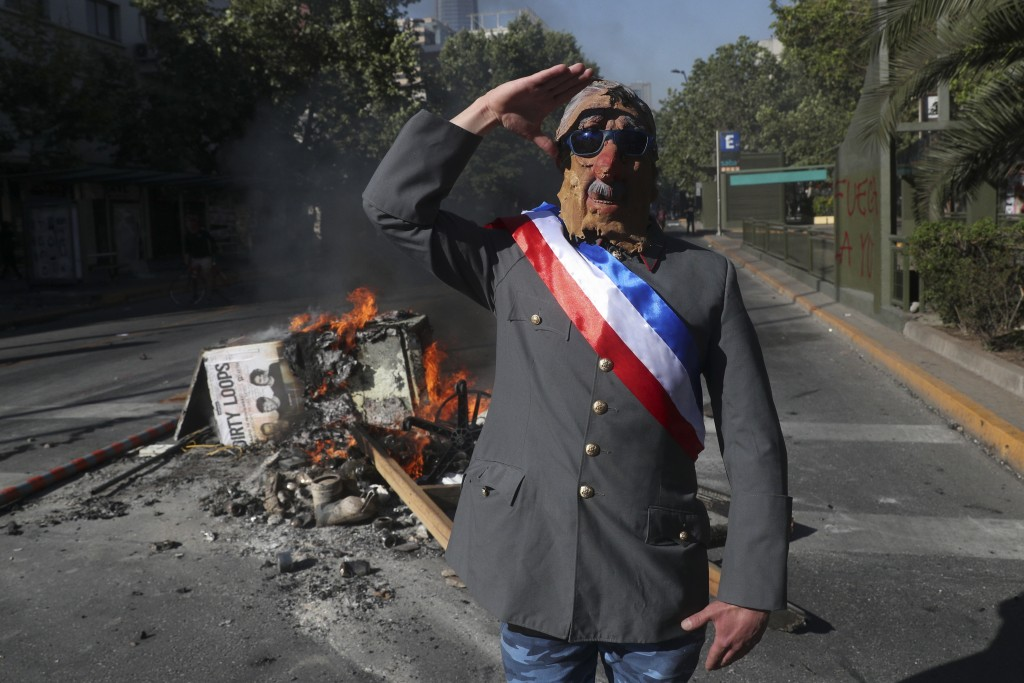 An anti-government demonstrator costumed as late military dictator Gen. Augusto Pinochet salutes in front of a burning barricade at a street in Santia...