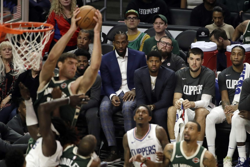 Los Angeles Clippers' Kawhi Leonard, center, and Paul George, third from right, watch from the bench during the second half of the team's NBA basketba...