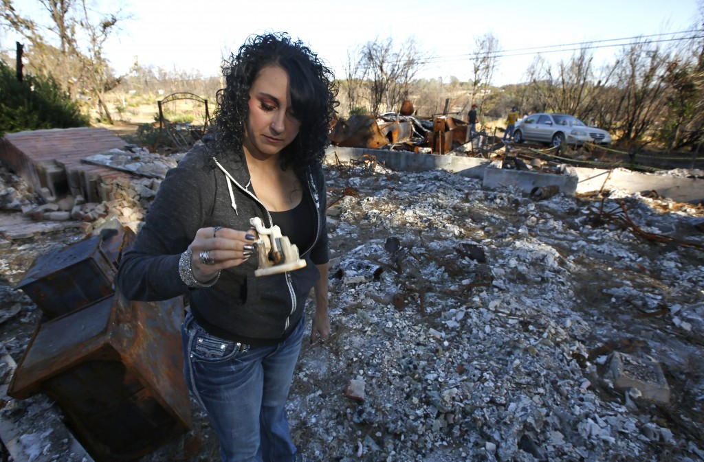 In this Friday, Oct. 18, 2019, photo, Amber Blood looks at a figurine she found in the ashes of her home lost in last year's Camp Fire in Paradise, Ca...