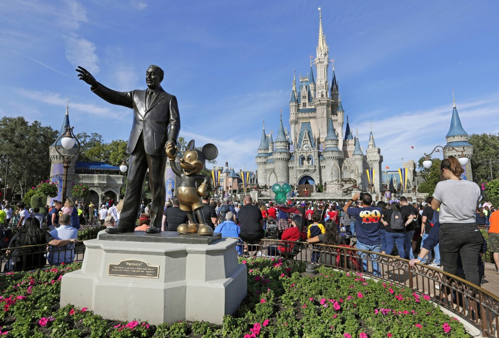 FILE - In this Jan. 9, 2019 file photo, guests watch a show near a statue of Walt Disney and Mickey Mouse in front of the Cinderella Castle at the Mag...