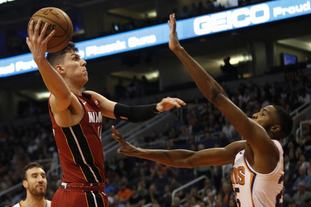 Miami Heat's Tyler Herro (14) drives to the lane against Phoenix Suns' Mikal Bridges (25) during the first half of an NBA basketball game Thursday, No...