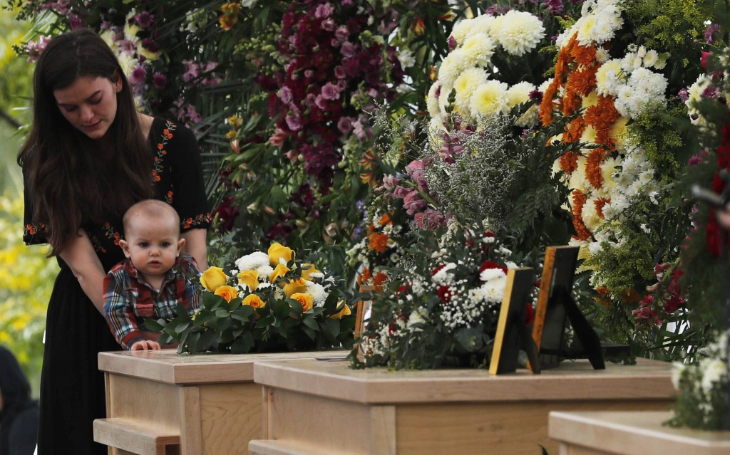 A woman and child stand by the coffins of Dawna Ray Langford, 43, and her sons Trevor, 11, and Rogan, 2, who were killed by drug cartel gunmen, during...