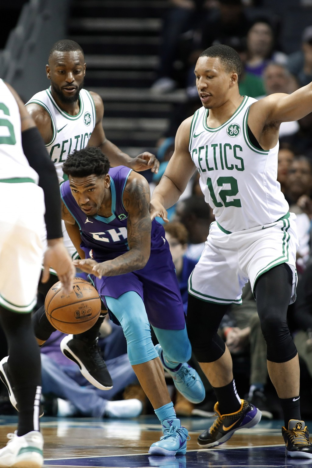 Charlotte Hornets' Malik Monk (1) dribbles away from Boston Celtics' Kemba Walker, left and Grant Williams, right, during the first half of an NBA bas...