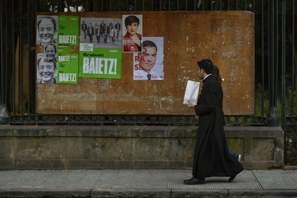 In this photo taken on Thursday, Nov. 6, 2019, a priest walks past electoral campaign posters of Spanish socialist candidate Pedro Sanchez, right, and...