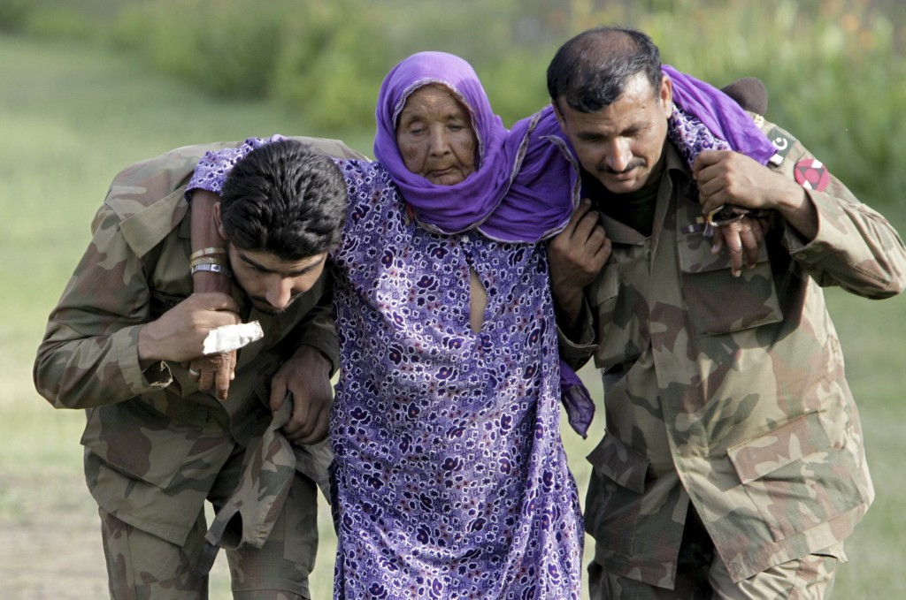 FILE - In this July 30, 2010, file photo, Pakistani army soldiers help an elderly villager evacuated from a flooded area in Nowshera, Pakistan. As Tur...