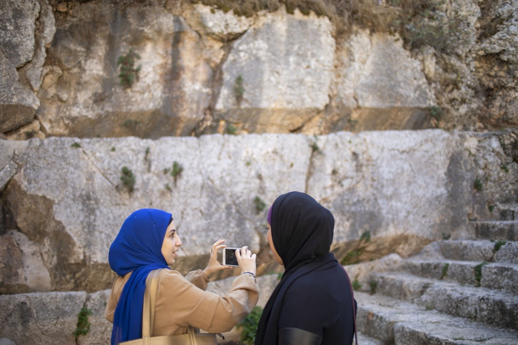 In this Thursday, Oct. 31, 2019 photo, Muslim women visits the Tomb of the Kings, a large underground burial complex dating to the first century BC, i...