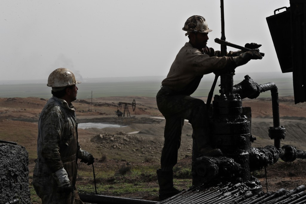 FILE - This March 27, 2018 file photo, shows Syrian workers fixing pipes of an oil well at an oil field controlled by a U.S-backed Kurdish group, in R...