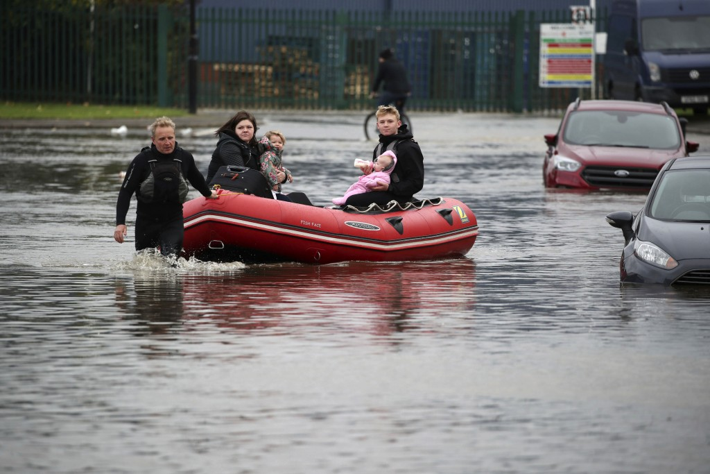 A young man feeds a child a bottle of milk as his father pulls an inflatable boat they have been using to rescue residents trapped by floodwater in Do...