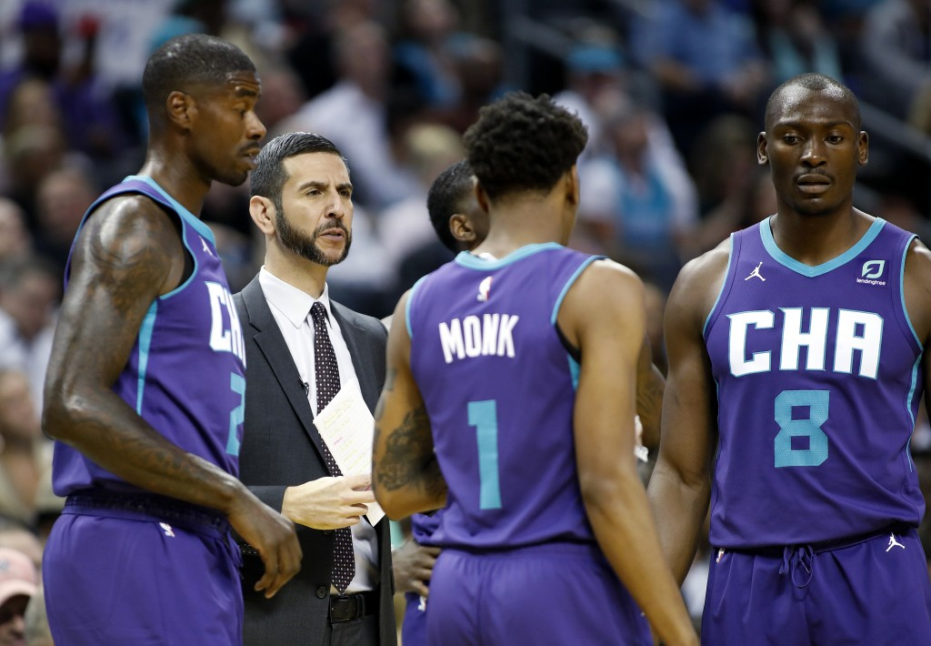 Charlotte Hornets coach James Borrego huddles with his team during a break in the first half of the team's NBA basketball game against the Boston Celt...
